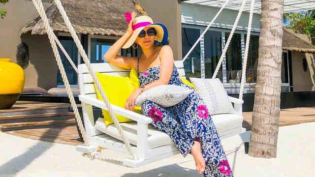 刘嘉玲穿印花吊带连体裤度假 躺沙滩椅惬意享受日光浴