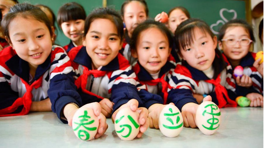 Students play game to make eggs stand upright on end in China's Hebei ahead of